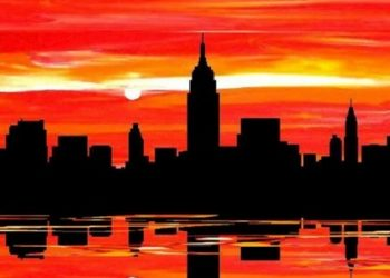Reflection of a city silhouette on water at sunset
